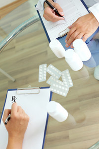 Image of practitioners hands prescribing tablets and vitamins