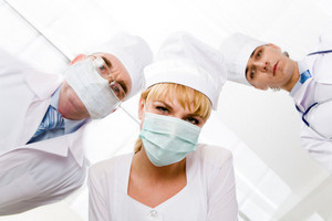 Image of pretty nurse in mask looking at camera with her colleagues at background
