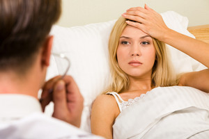Image of pretty woman in bed touching her forehead and looking at doctor