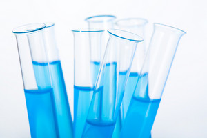 Image of several medical flasks with blue water on a white background