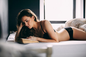 Image of young brunette in lingerie lying on her bed reading novel. Attractive female model relaxing in bedroom.