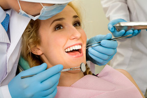 Image of young lady with dentist over her before checking oral cavity