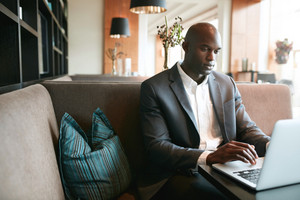 Image of young man sitting at cafe working on laptop. African businessman at coffee shop surfing internet on laptop.