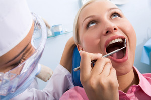 Image of young woman during inspection of oral cavity with help of mirror