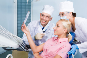 Image of young woman looking at mirror at her teeth surrounded by dentist and assistant