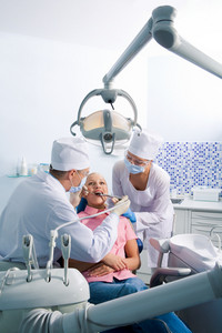 Image of young woman sitting on chair during oral sanitation surrounded by dentist and nurse