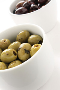 Green And Black Olives In White Dishes