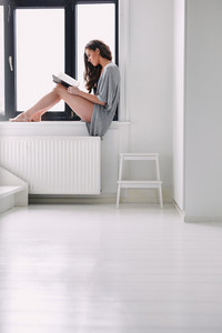 Indoor shot of young woman sitting on window sill and reading a book. Caucasian female model in nightwear busy reading a novel by window at home.