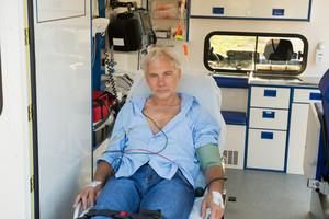 Injured senior man sitting on stretcher in ambulance car