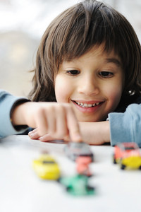 Innocence, childhood concept - playing with toy car
