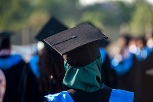 Islamic woman with graduate cap standing from behind