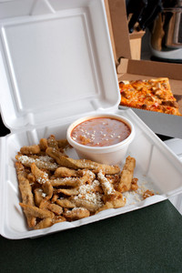 Italian fast food in takeout containers.  Pizza and fried battered eggplant strips.