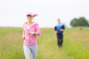 Jogging young fit couple running field meadow in sportswear tracksuit