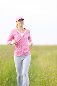 Jogging young fit woman running park field in sportswear tracksuit