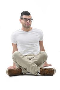 Joyful boy in white shirt sitting isolated on white