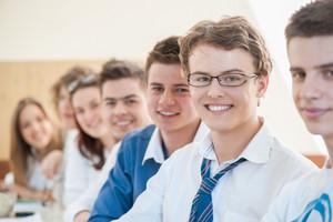 Joyful group of teenagers posing in a classroom