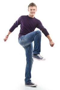 Joyful male model posing standing on one foot