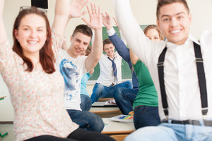 Joyful students holding waving their arms in a classroom