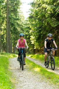 Joyful young biker couple in woods