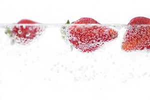 Juicy red strawberries plunging into some carbonated water.  Shallow depth of field.