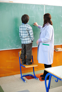 Kid and his teacher in classroom