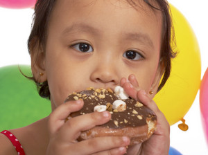 Kid Eating A Donut At A Party