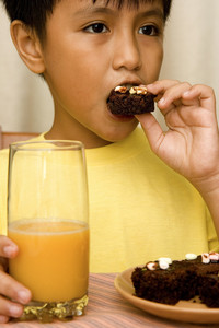 Kid Eating Brownies And Drinking Orange Juice