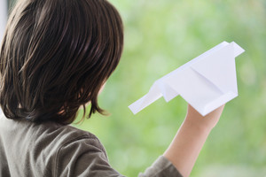 Kid holding a paper airplane and dreaming about flying