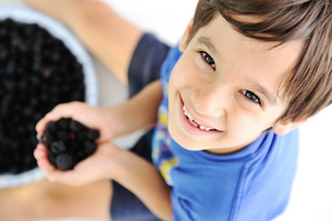 Kid holding blackberry picking and smiling
