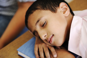 Kid in classroom on desk falling asleep on his notebook