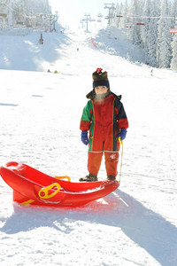 Kid on snow with sledge, frozen breath comming out of his mouth :)