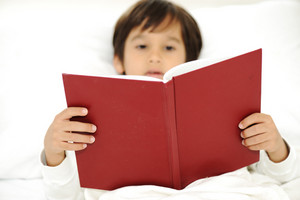 Kid reading book in bed (focus on the book)