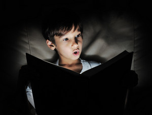 Kid reading book, light in darkness