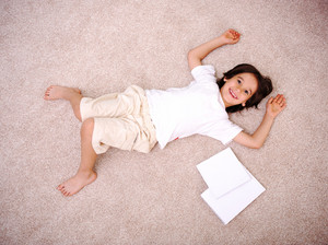 Kid reading for school lying on floor at home