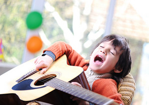 Kid singing and playing guitar at home