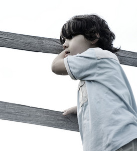 Kid standing on fence outdoors