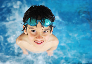 Kid with swimming glasses in water pool
