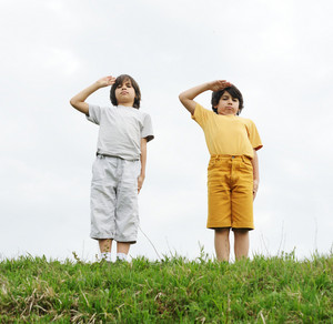 Kids saluting on a green meadow