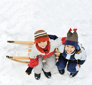 Kids sliding sledge in the snow sitting