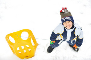 Kids sliding sledge in the snow