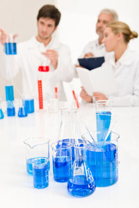 Laboratory - beaker with blue liquid,scientists in backgroud