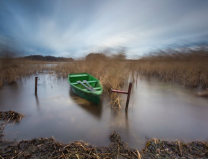 Lake with boat. long exposure landscape. Autumnal bad weather landscape photographed on polish lake.--