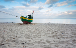 Landscape with Baltic Sea. Fishing boat on the beach. Tranquil evening landscape. Long exposure photo--