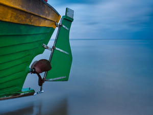 Landscape with Baltic Sea. Fishing boat part on the beach. Tranquil evening landscape. Long exposure photo