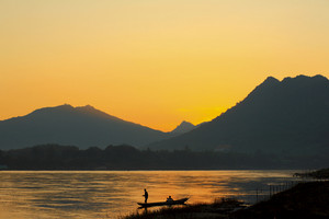 Laos fisherman at river on sunset