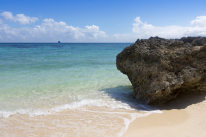 Large rock on a white sand beach