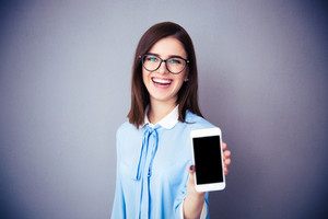Laughing businesswoman showing blank smartphone screen
