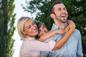 Laughing family hugging outside