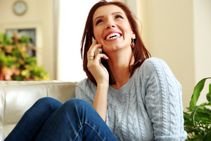 Laughing woman talking on the phone and looking up at home