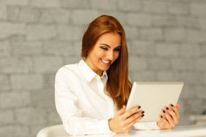 Laughing young businesswoman looking at tablet computer screen